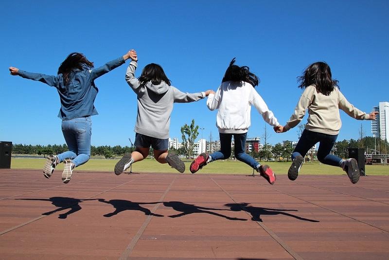 4人の少女達が手を繋ぎ高くジャンプしている