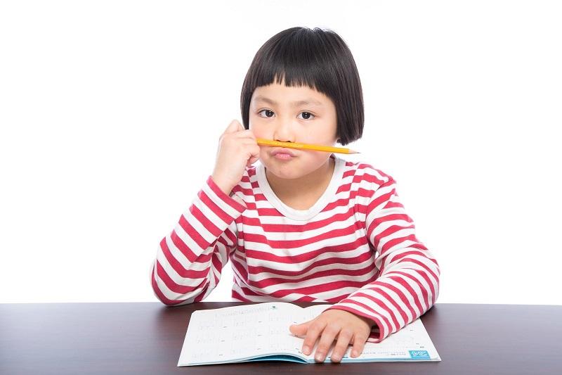 少女が鉛筆を咥え、勉強をしている