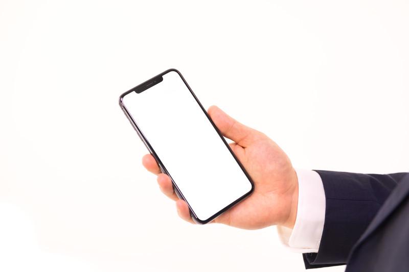 スマートフォンを手で持っている