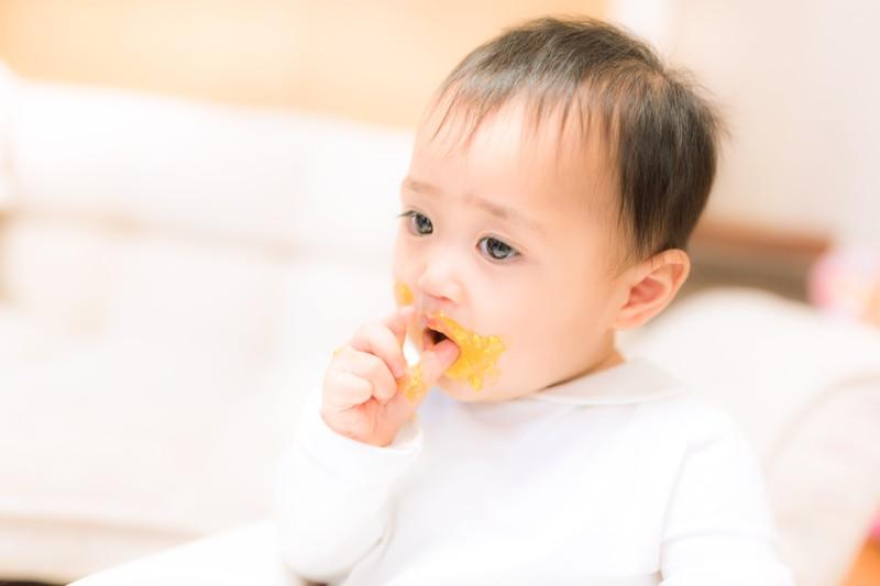 離乳食を食べて口の周りがベタベタな赤ちゃん