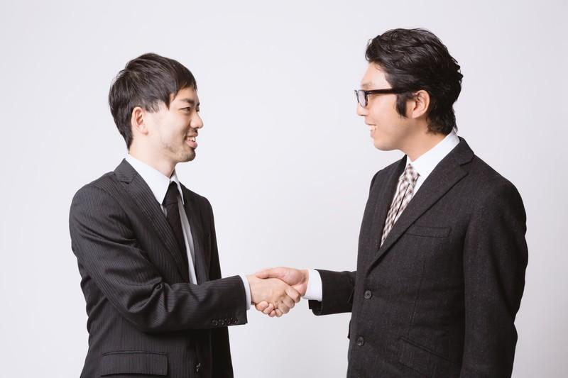 他者と握手してコミュニケーションをとる男性