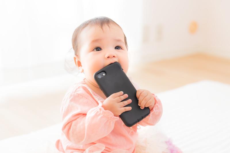 スマートフォンを咥える赤ちゃん