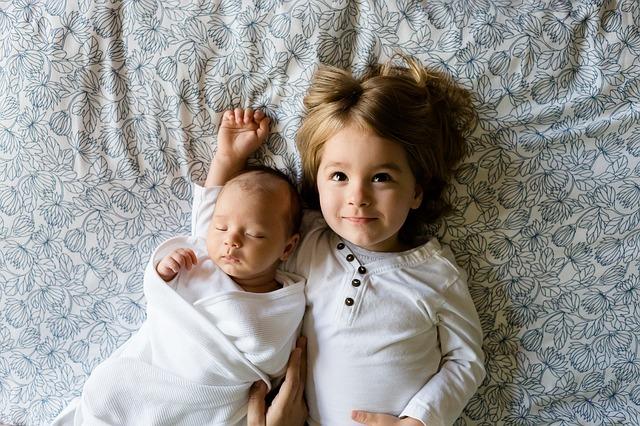 寝ている赤ちゃんを腕枕して嬉しそうな少女
