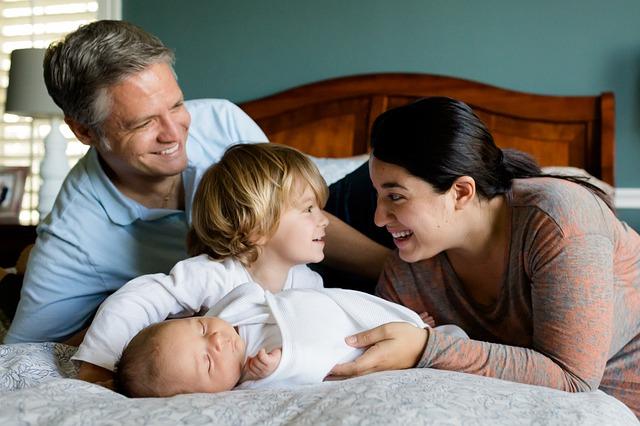 生まれたての赤ちゃんをその母親とお兄ちゃんとお父さんが囲んで嬉しそうにしている