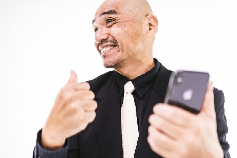 スマートフォンを見て喜ぶ男性の画像