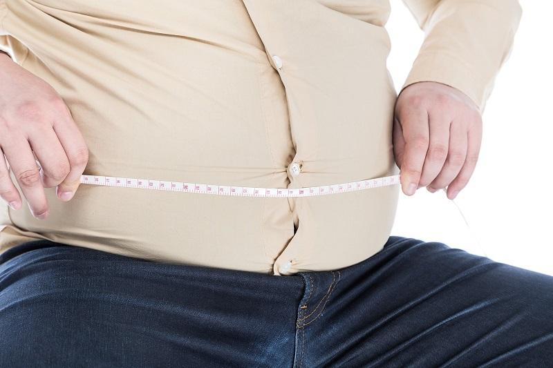 太ったお腹周りをメジャーで測る男性