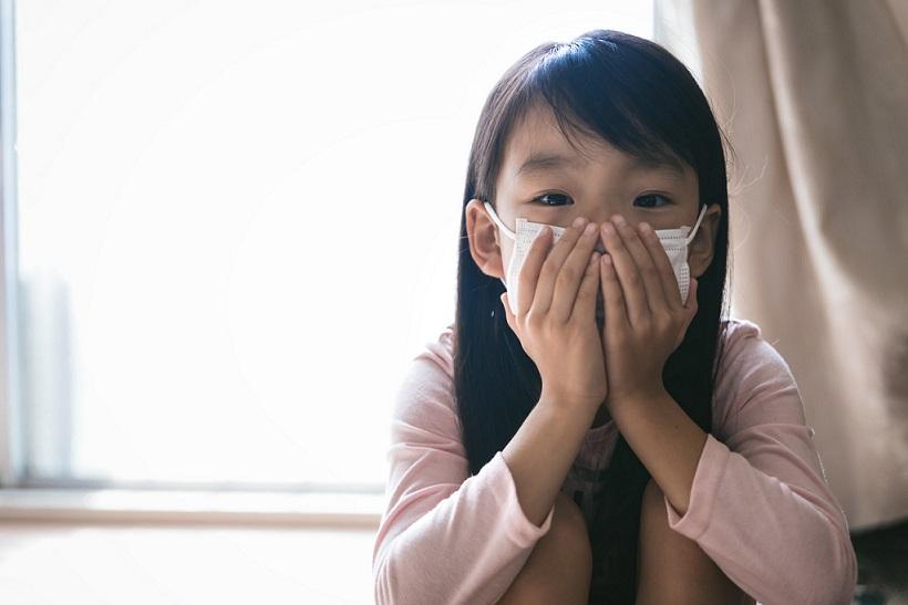 マスクをして口元を抑える少女