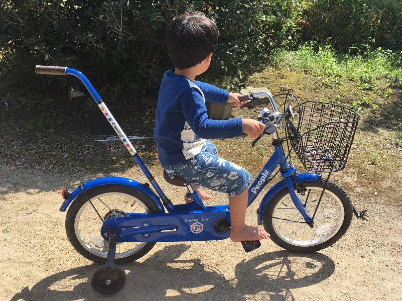 少年が自転車に乗っている足をペダルに乗せている