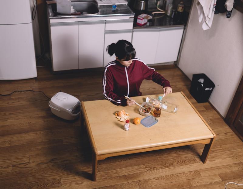 アパートで一人食事をする女性