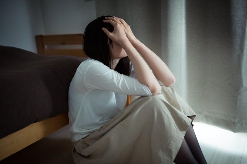 薄暗い部屋で座り込み、頭を抱える女性