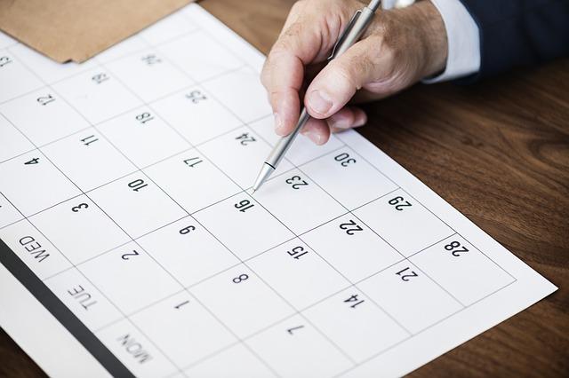 カレンダーの16日の日付の上をボールペンで指している