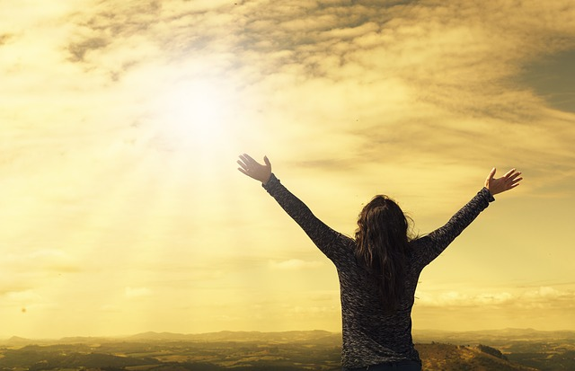 朝日に向かって両手を大きく広げる女性